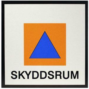 Bild på skylt med en blå triangel i en orange kvadrat och ordet skyddsrum